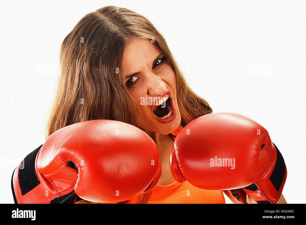 Portrait of young woman with red boxing gloves  Angry female fighting - Stock Image