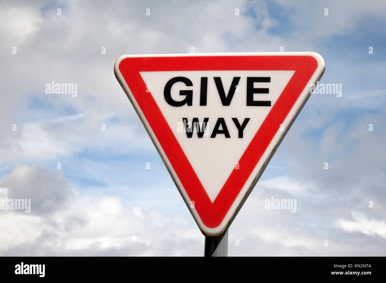 Give Way Sign against blue sky background Stock Photo