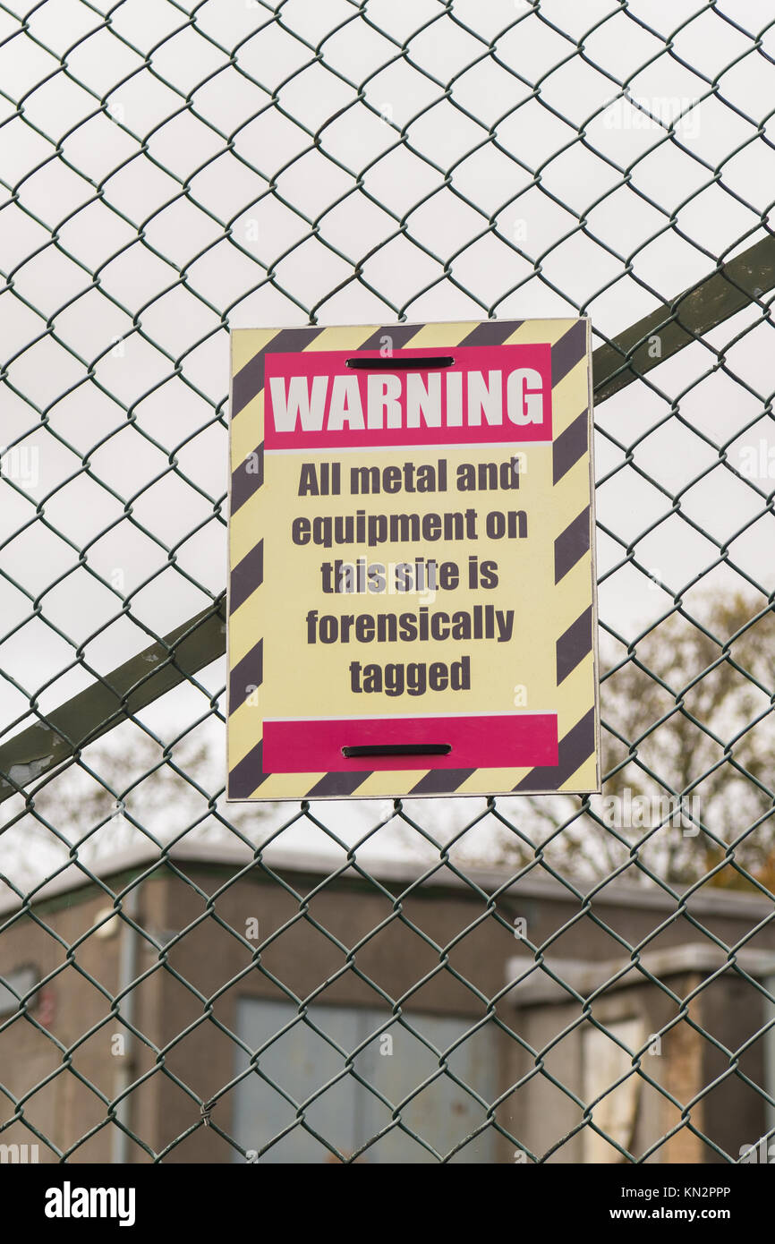 Warning All metal and equipment on this site is forensically tagged sign on security fence in Edinburgh, Scotland, - Stock Image