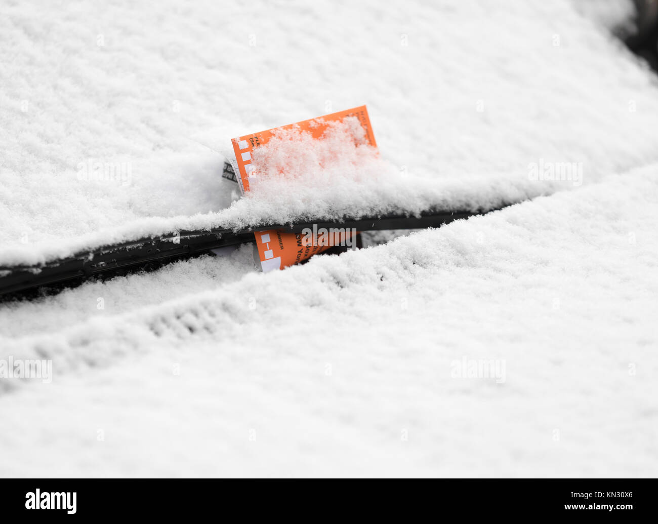 Parking violation ticket on snow covered car windshield Stock Photo
