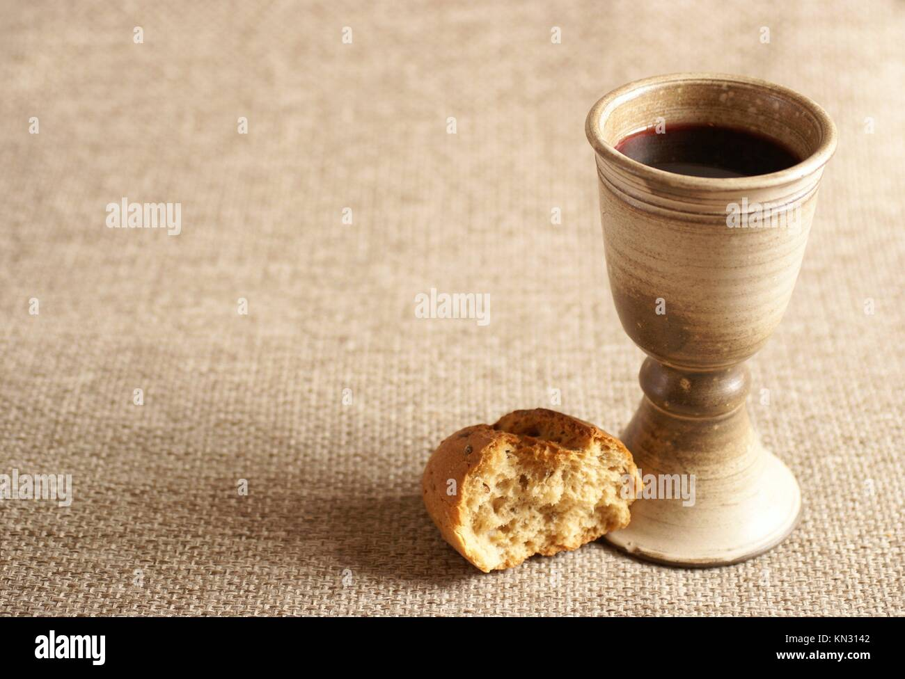 Chalice with wine and bread. Background with copy space. - Stock Image
