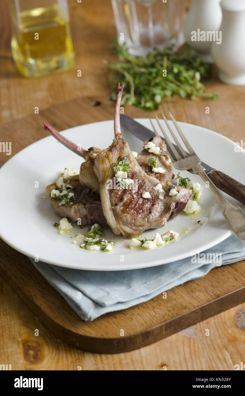 Grilled lamb chops with crumbled feta and herbs on a plate. - Stock Image