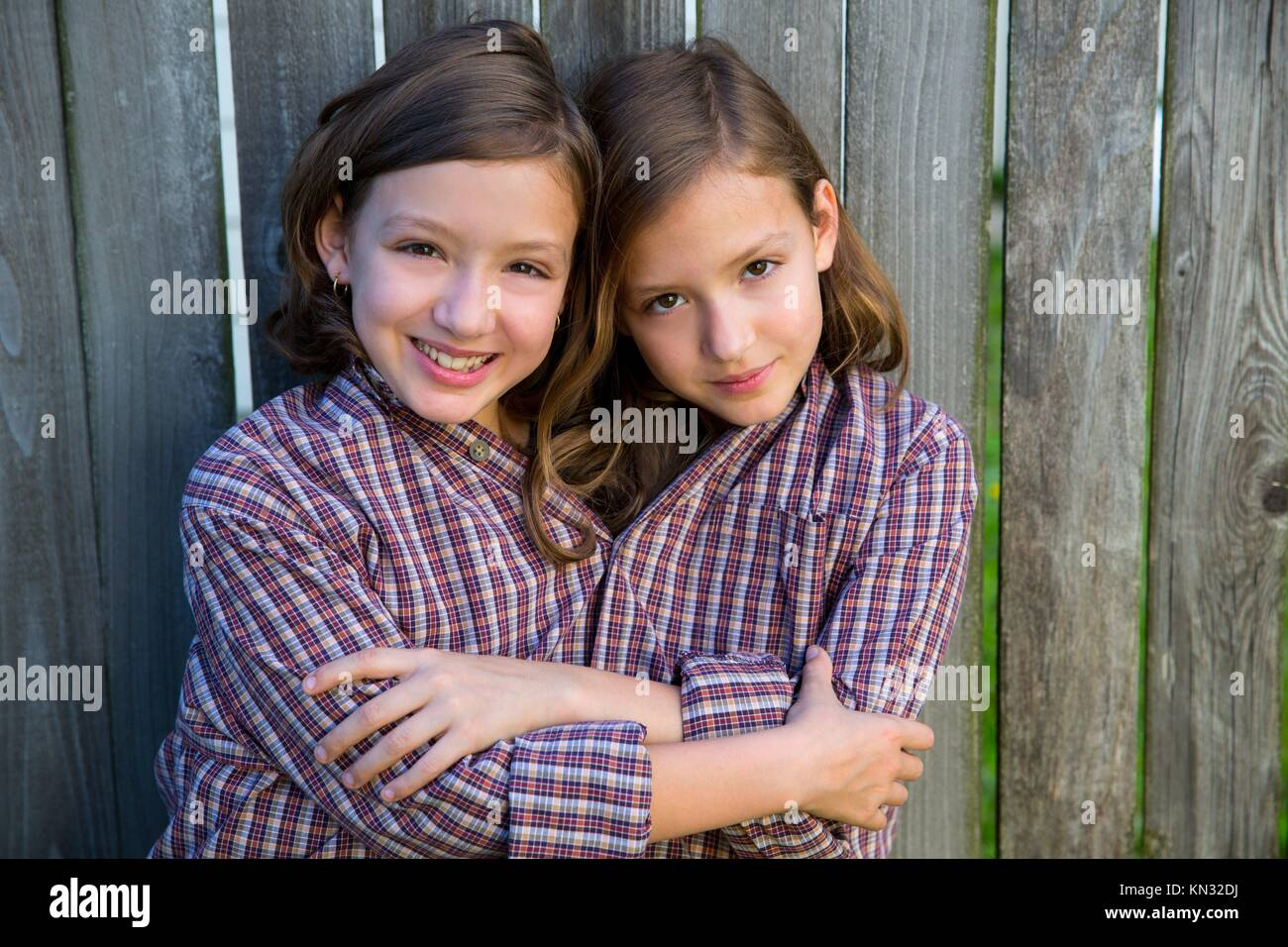 twin girls fancy dressed up pretending be siamese with his father shirt. - Stock Image