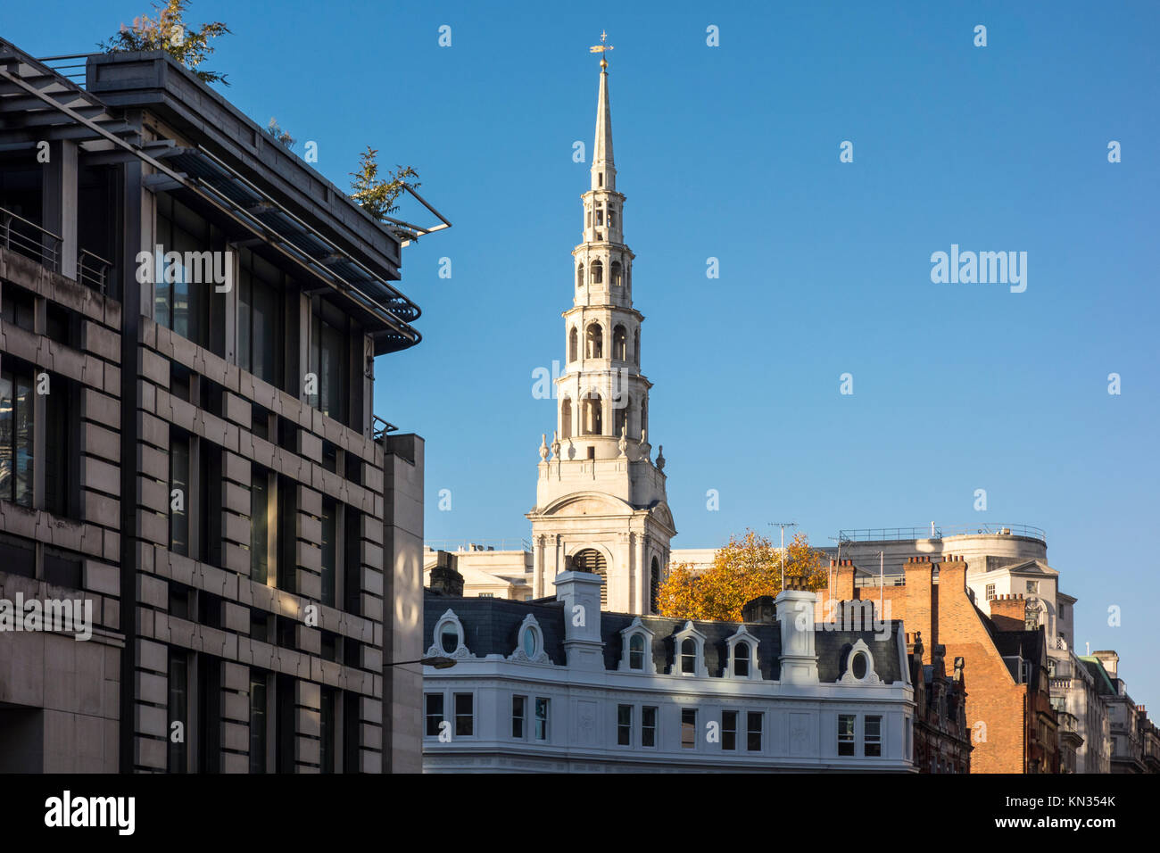 Spire of St Bride's Church, Fleet Street, viewed above the rooftops of buildings on Ludgate Circus. City of - Stock Image