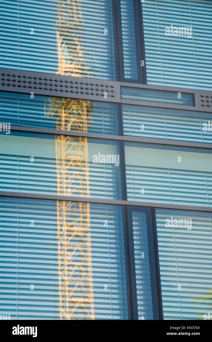 glass facade reflecting construction crane - Stock Image