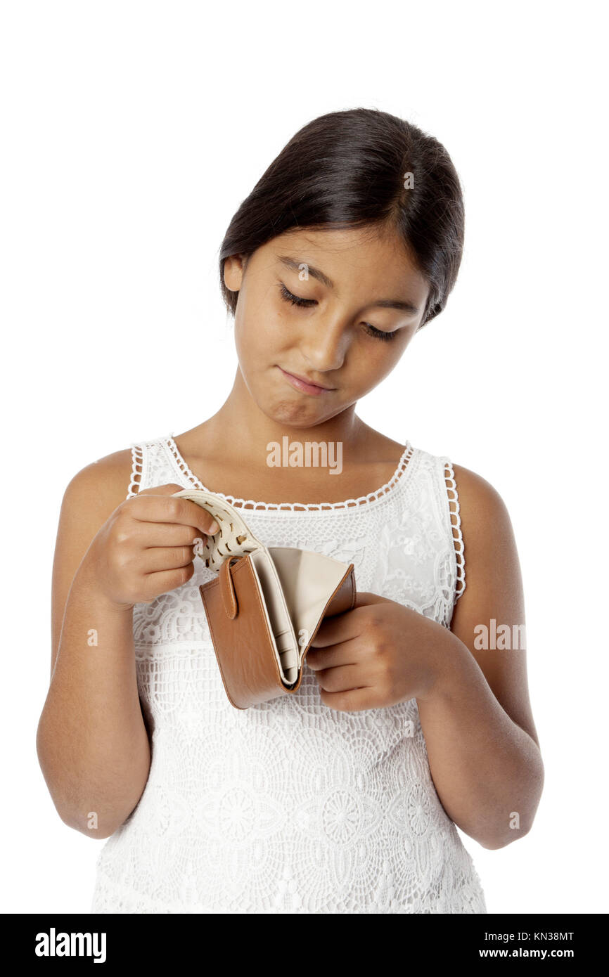 Young broke teenage girl looking into her empty wallet on white background. - Stock Image