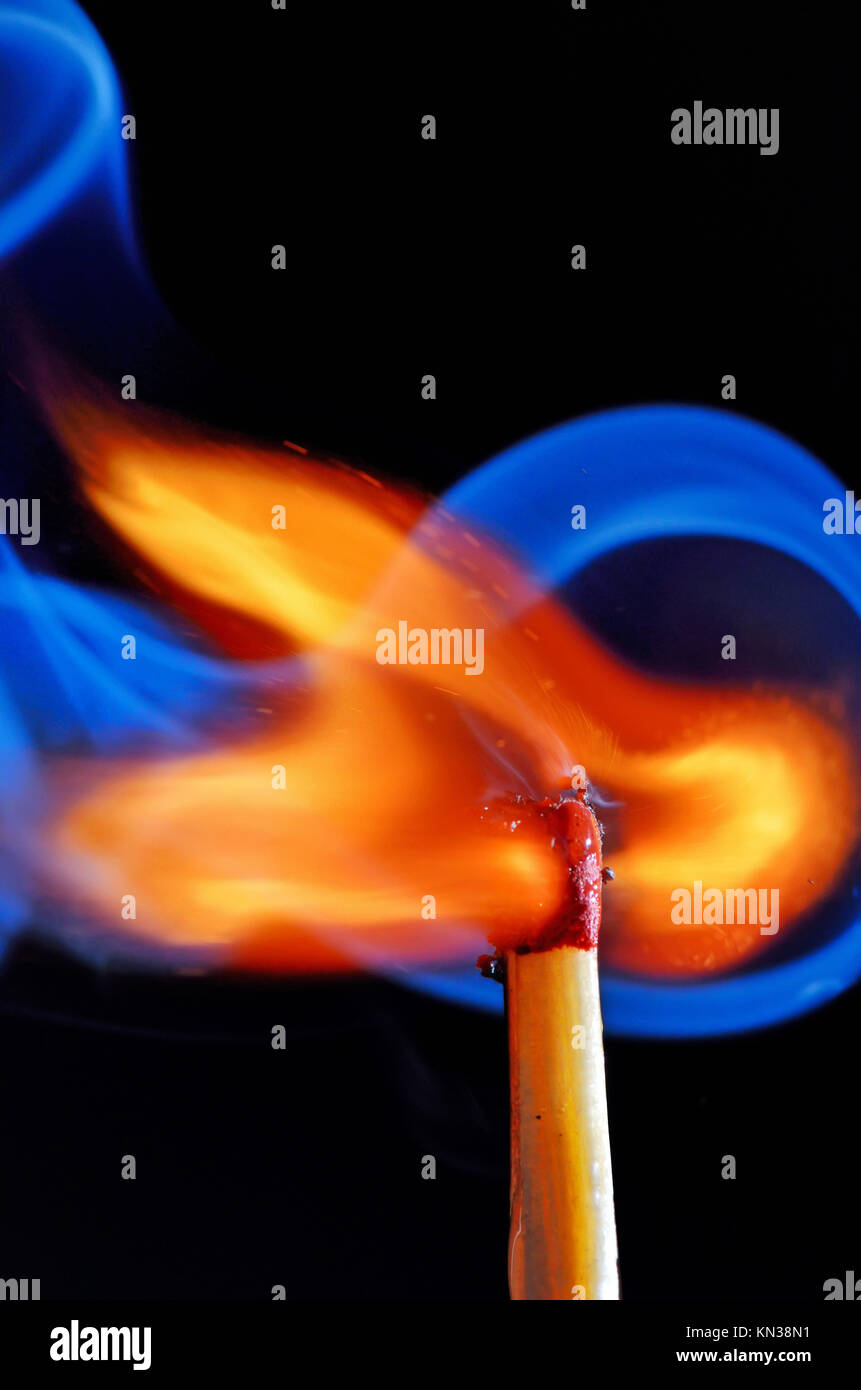 lighting a match on black background Stock Photo