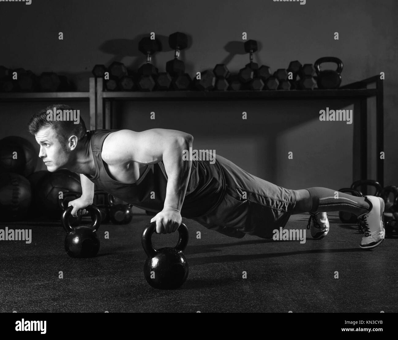 Kettlebells push-up man strength pushup exercise workout at gym. - Stock Image