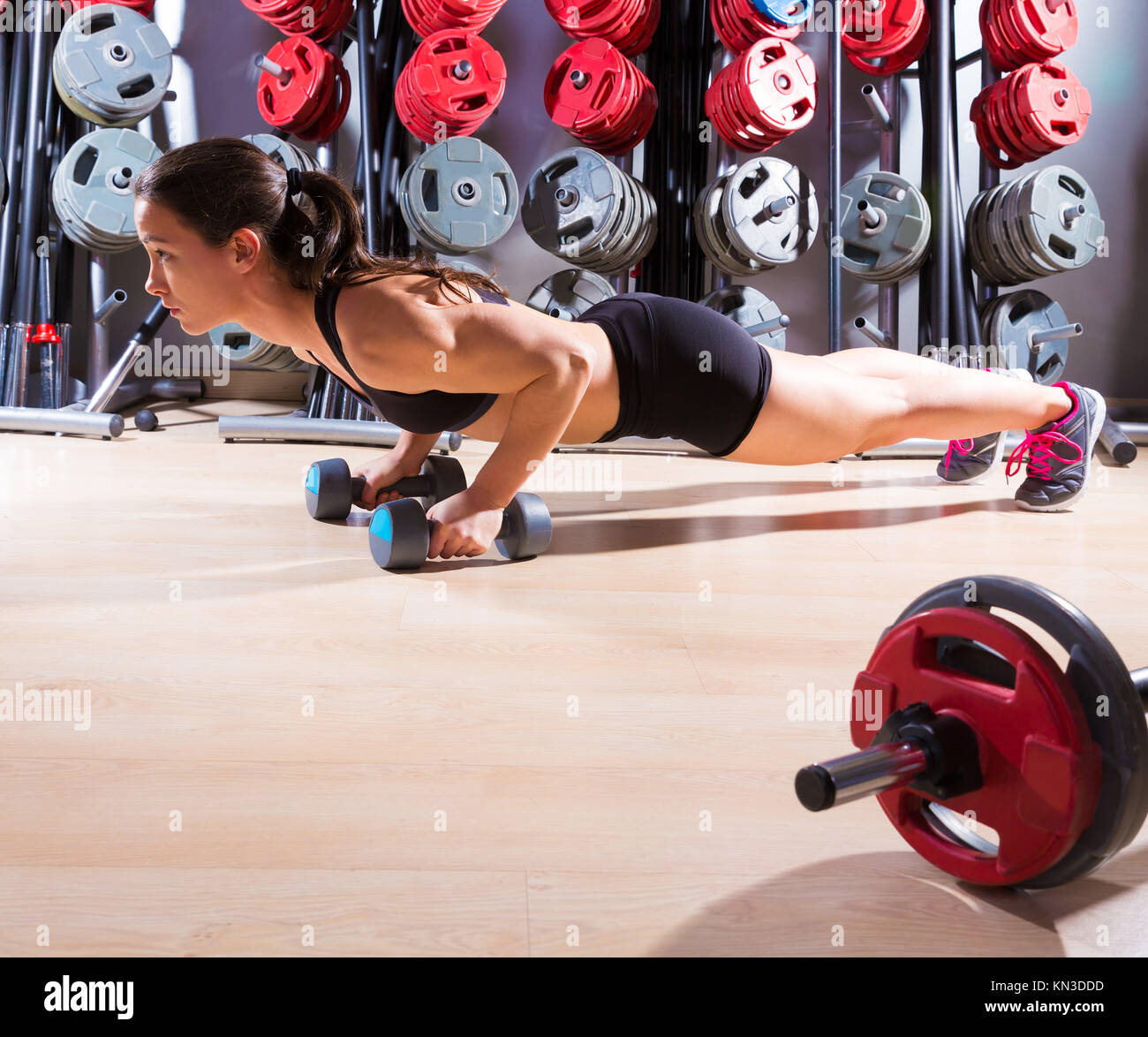 Push-ups woman with dumbbells workout fitness club at weightlifting gym. - Stock Image