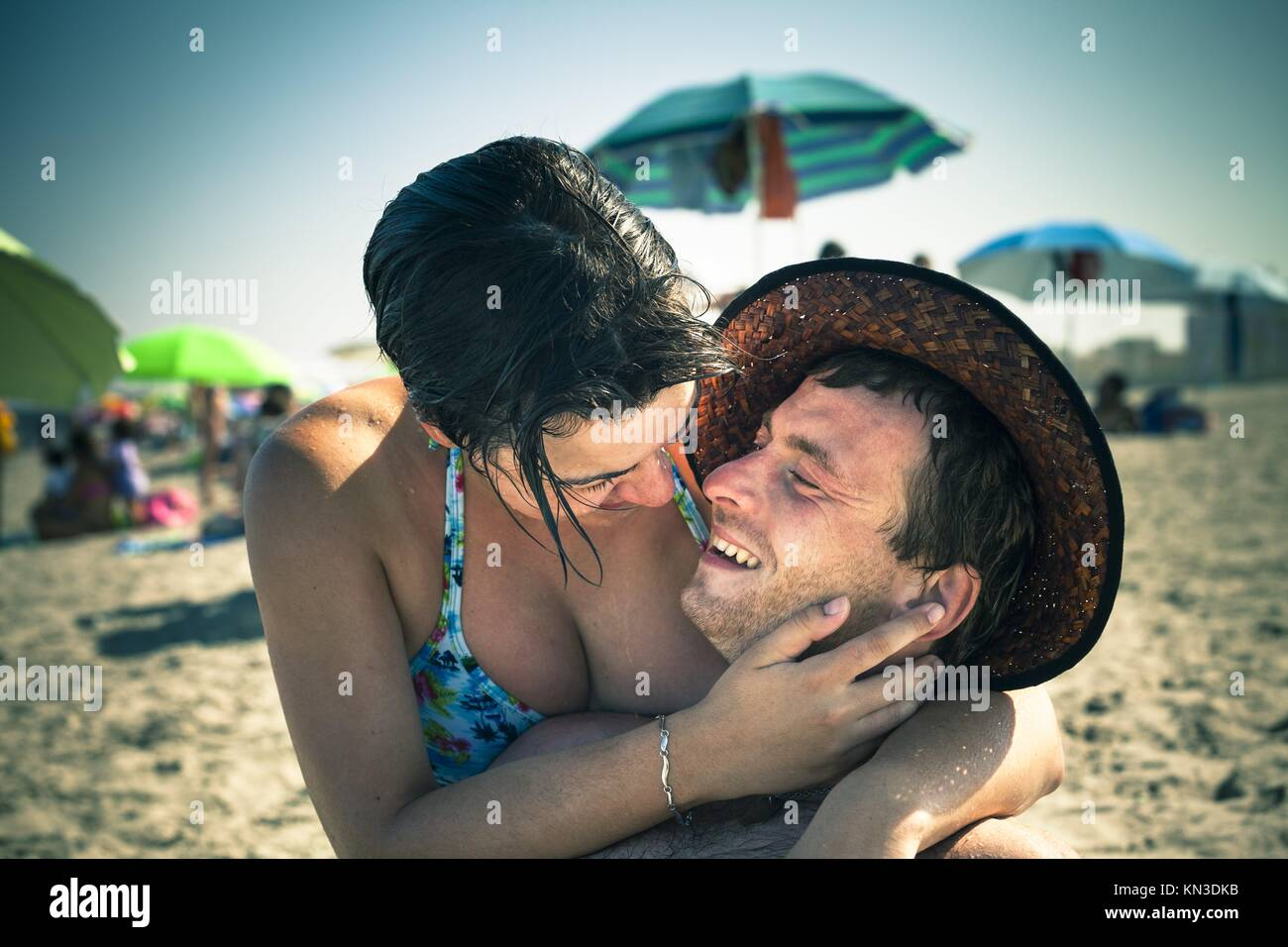 Happy lovers enjoying sunny day on the beach. - Stock Image