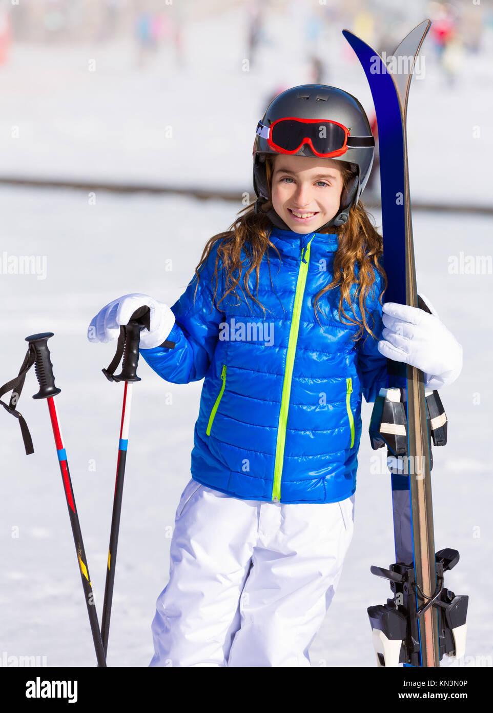 Kid girl winter snow with ski equipment helmet goggles poles. - Stock Image