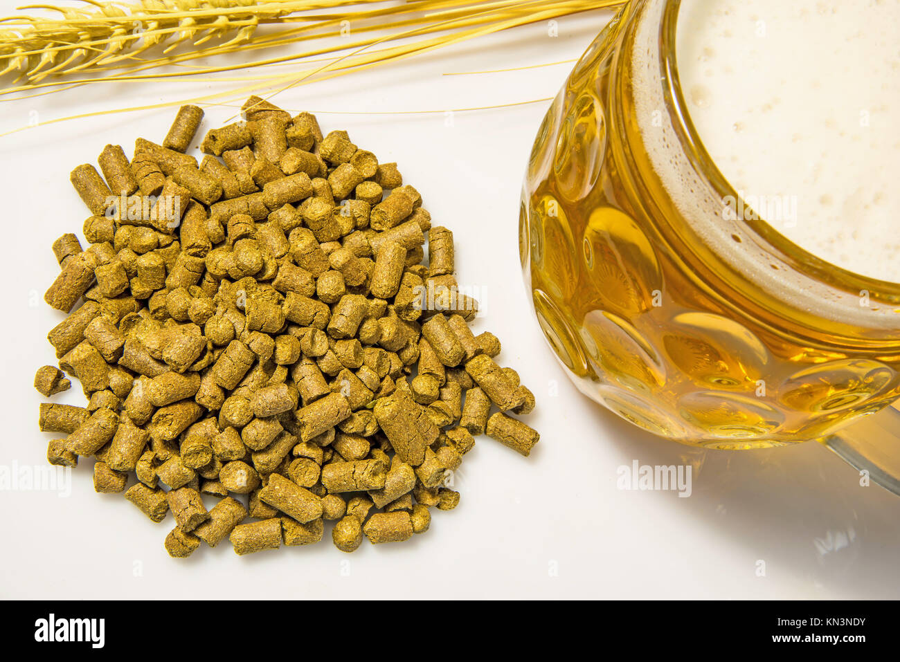 Hops pellets with beer glass. - Stock Image