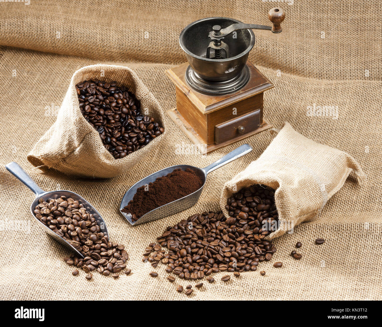 still life of coffee beans in jute bags with coffee grinder. - Stock Image