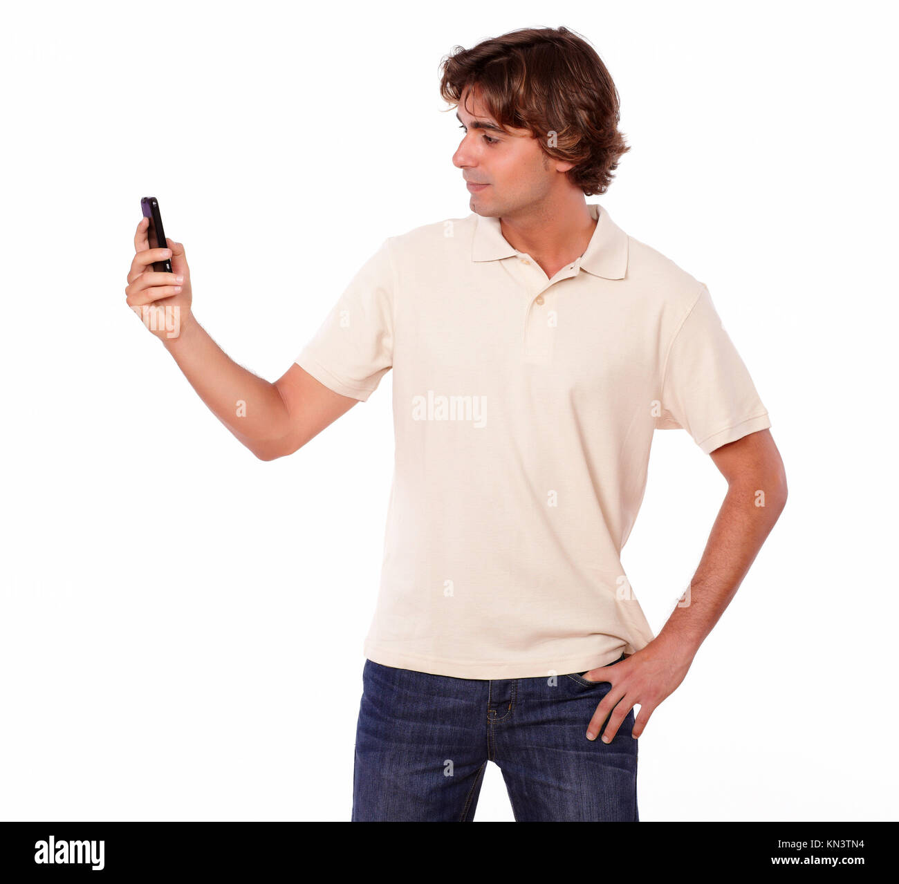 Portrait of a latin man in jeans reading on cellphone on white background. - Stock Image