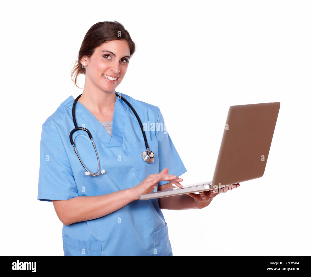 Portrait of a pretty nurse smiling at you, while using her laptop, against white background. Stock Photo