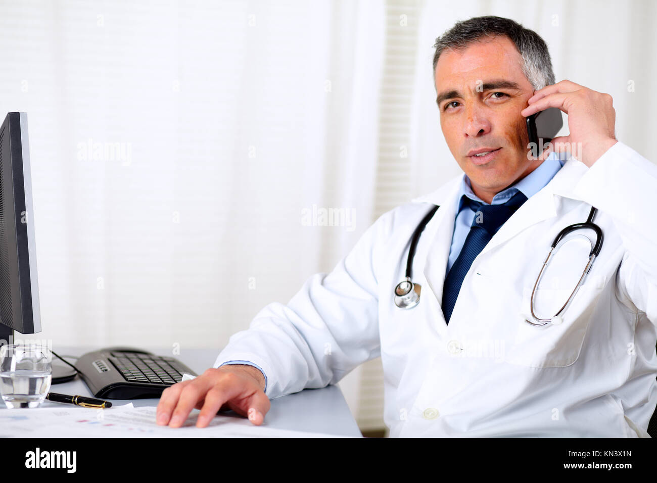 Portrait of a professional friendly senior doctor using a mobile phone. - Stock Image