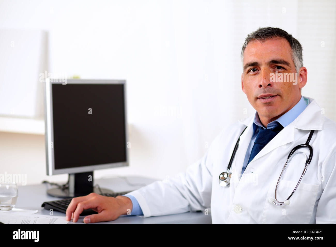 Portrait of a professional mature medicine specialist at hospital workplace. - Stock Image
