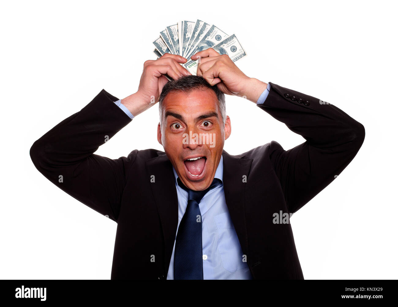 Portrait of a victorious mature person having fun with the earned money and wearing a black suit on isolated background. - Stock Image