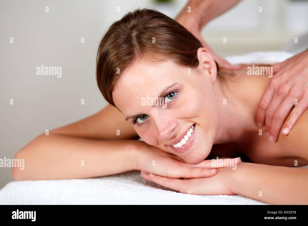 Portrait of a lovely pretty girl smiling and relaxing while getting a massage from a professional masseuse at spa Stock Photo