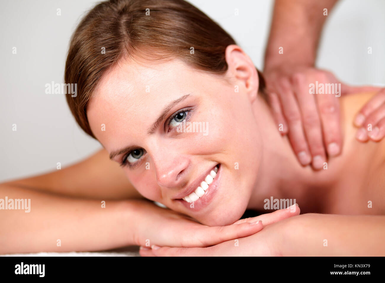 Close-up portrait of a lovely pretty woman smiling and relaxing while getting a massage from a professional masseuse Stock Photo