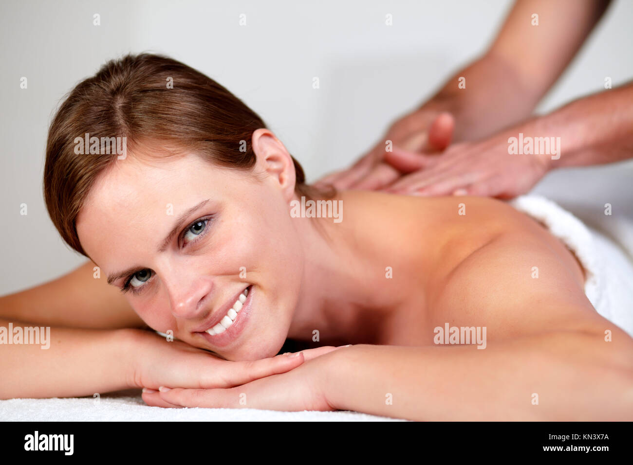 Close-up portrait of a young pretty woman smiling and relaxing while getting a massage from a professional masseuse Stock Photo