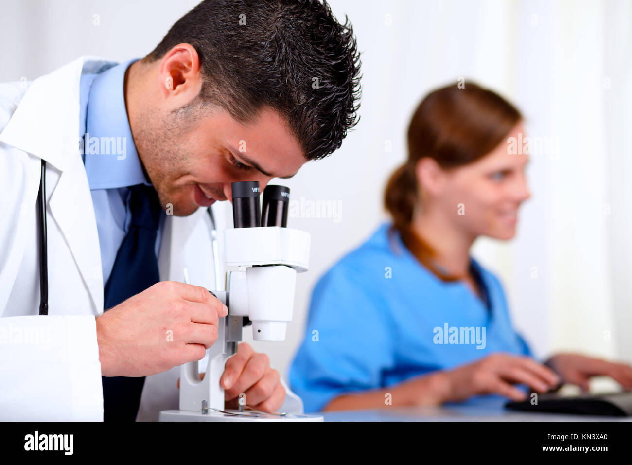 Portrait of two medical colleagues working at laboratory at hospital. - Stock Image