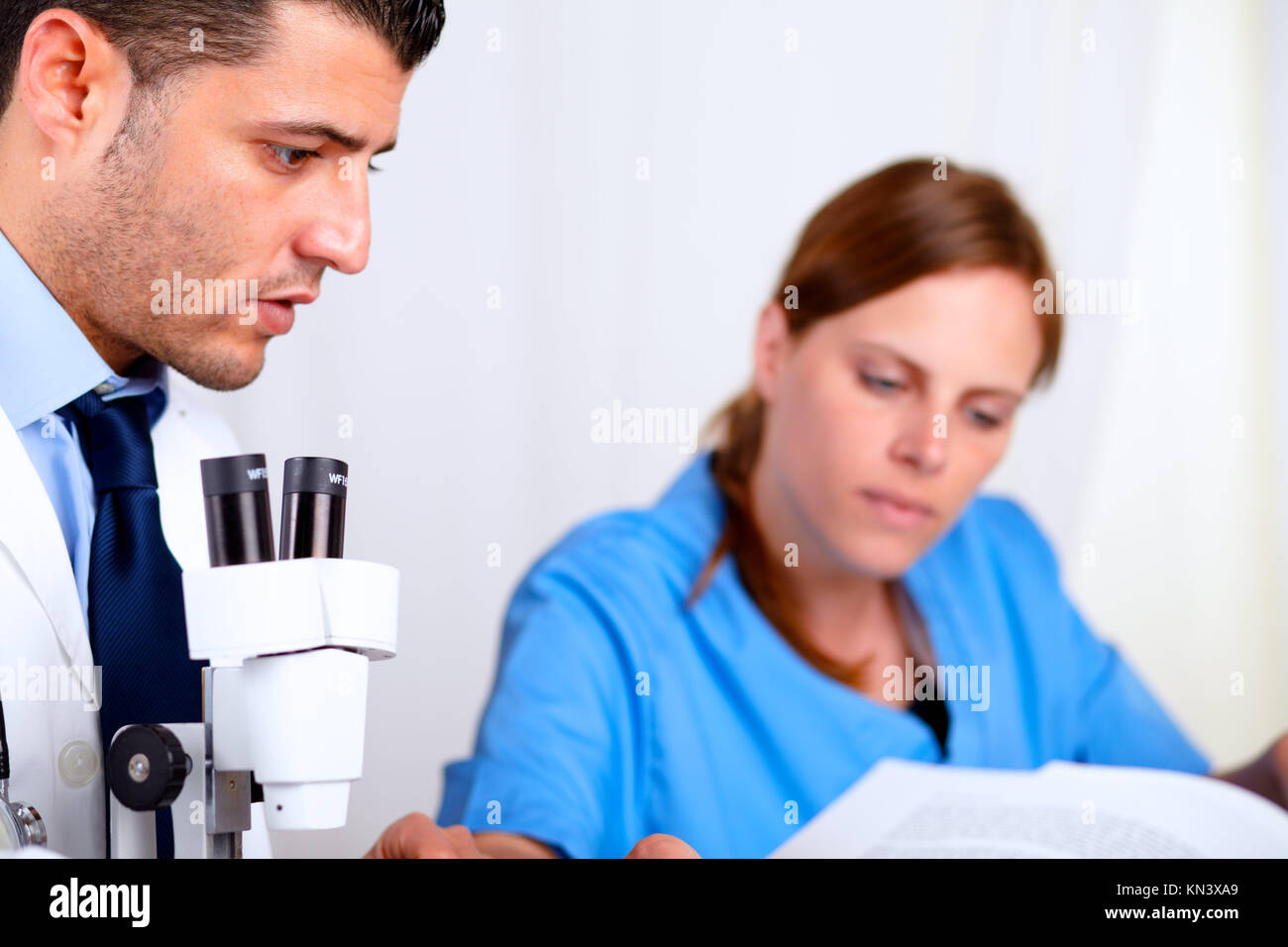 Portrait of two colleagues working at laboratory at hospital indoor. - Stock Image