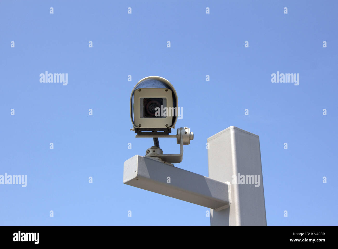 Modern outdoor surveillance camera aiming straight at the beholder. - Stock Image