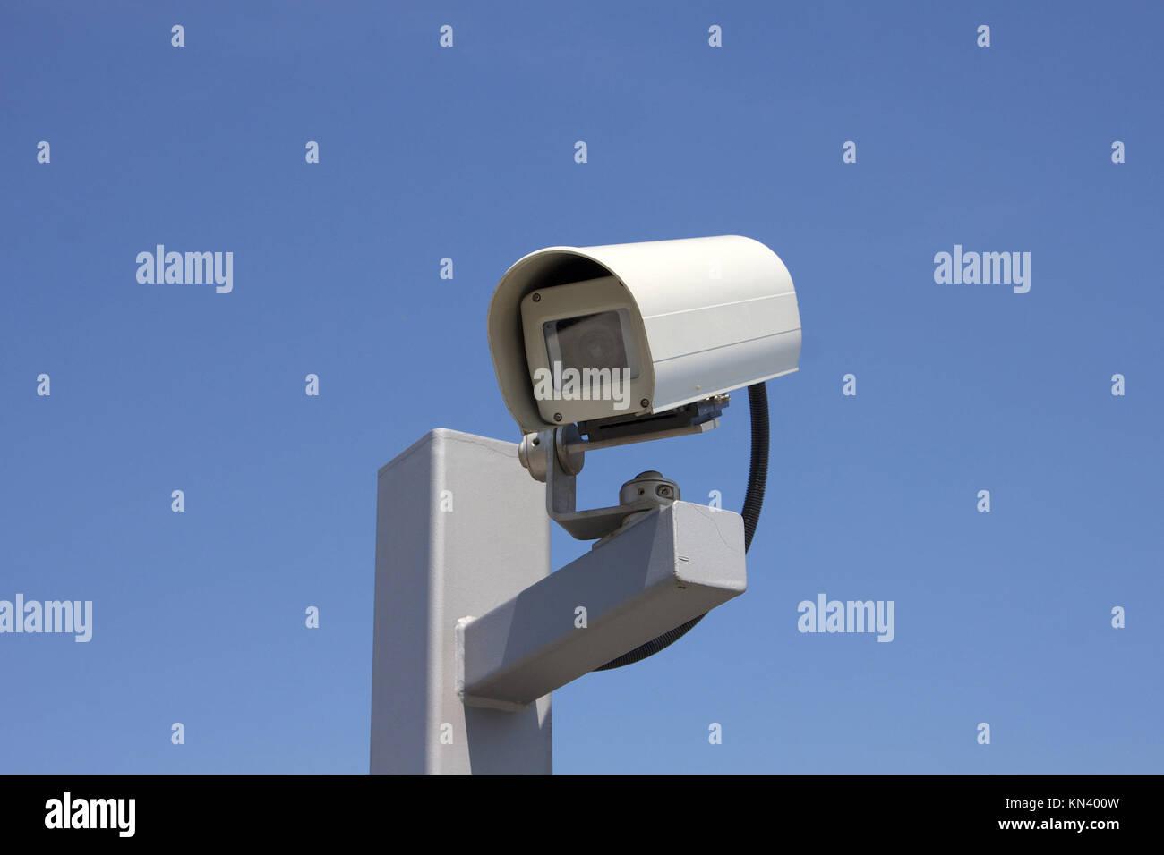 Modern outdoor surveillance camera facing left. - Stock Image