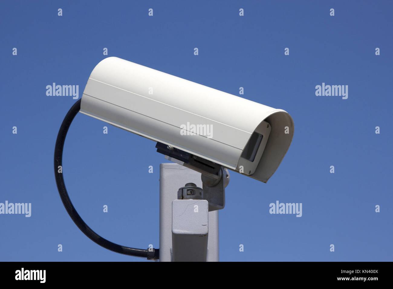 Close-up of modern outdoor surveillance camera facing right. - Stock Image