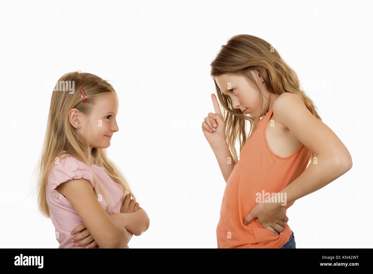 Big sister disagree pointing finger at her little sister because she did a silly, foolish, stupid thing or something - Stock Image