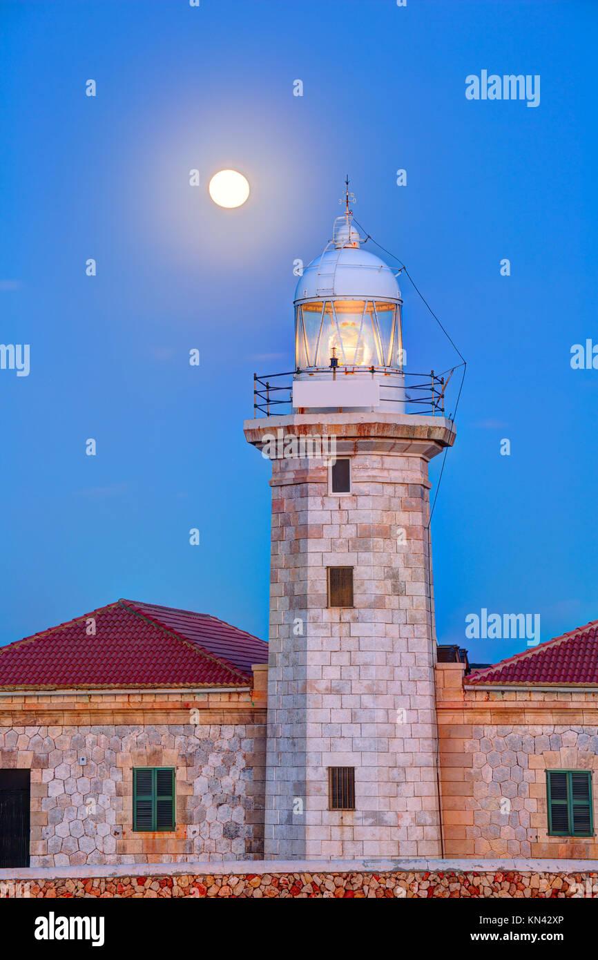 Ciutadella Menorca Punta Nati lighthouse with moon shining in sky. - Stock Image