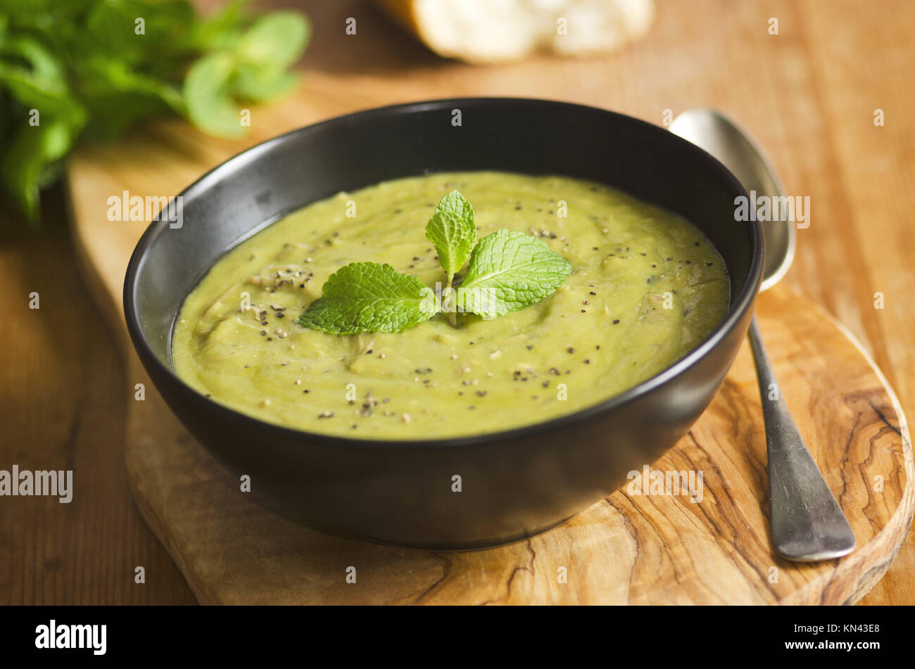 Garden pea and shredded ham soup in a bowl. - Stock Image