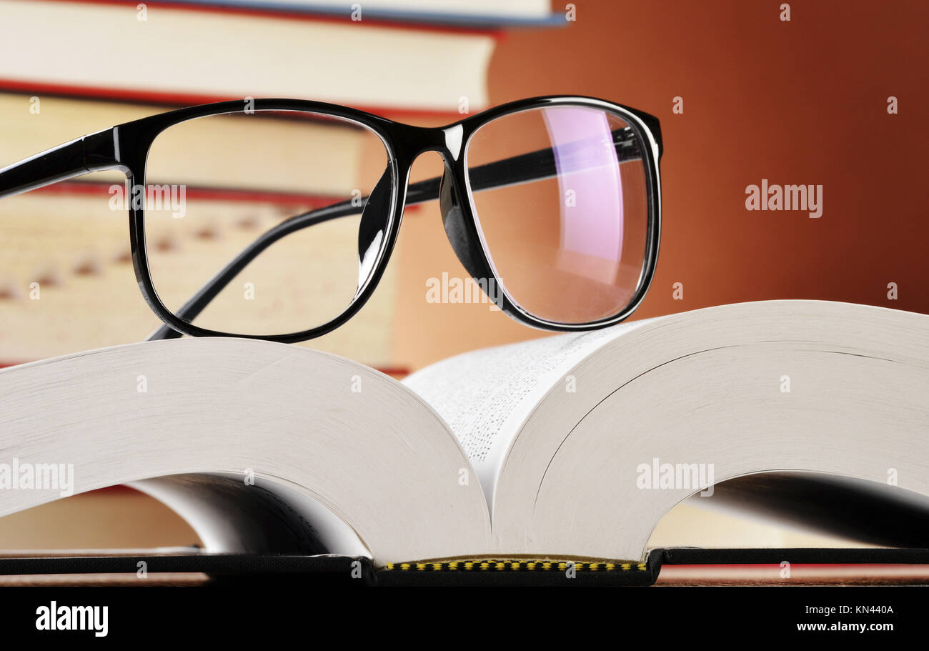 Composition with glasses and books on the table. - Stock Image