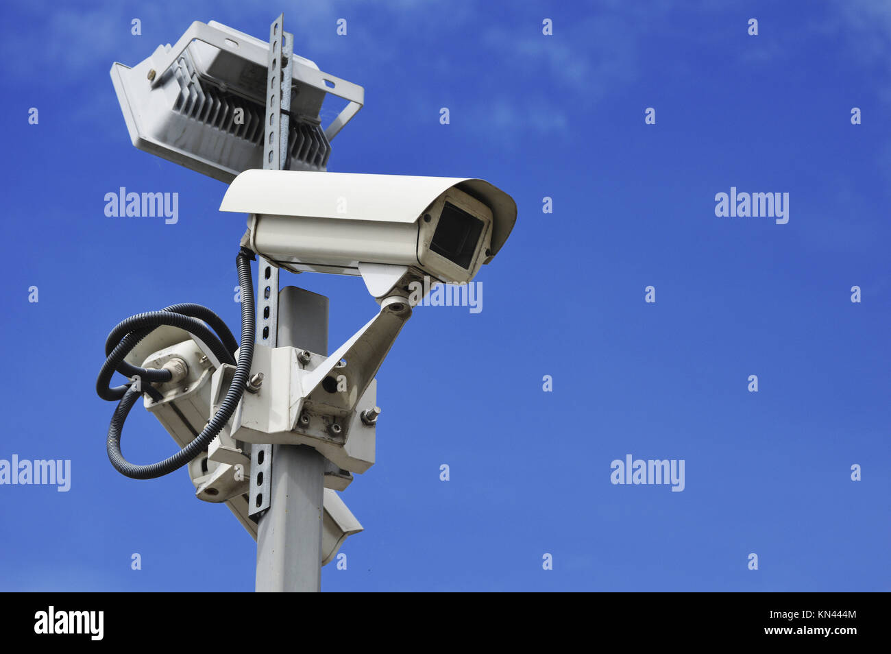 Hi-tech dome type camera over a blue sky. - Stock Image