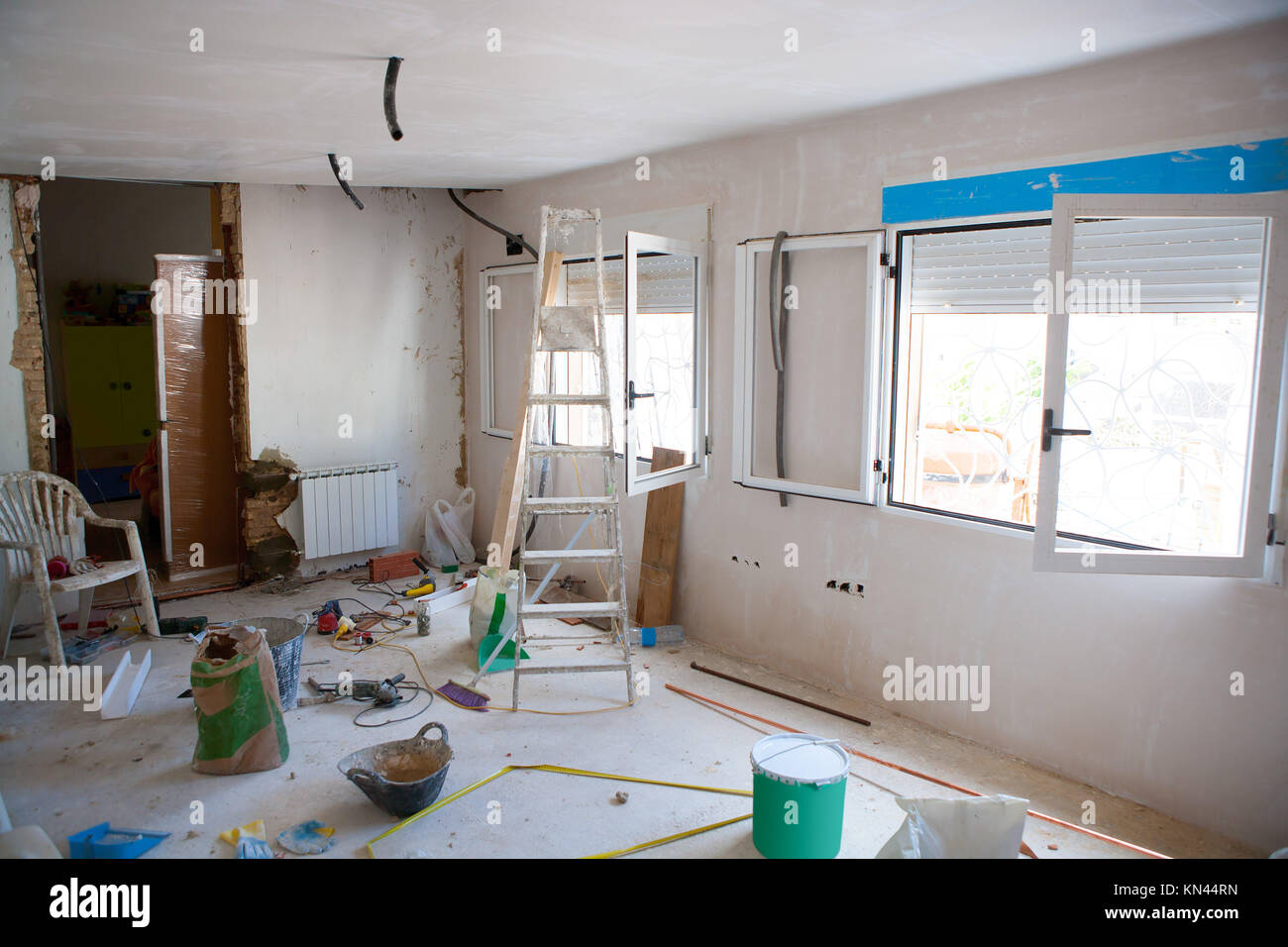 House indoor improvements in a messy room construction with plaste tools and ladder. - Stock Image