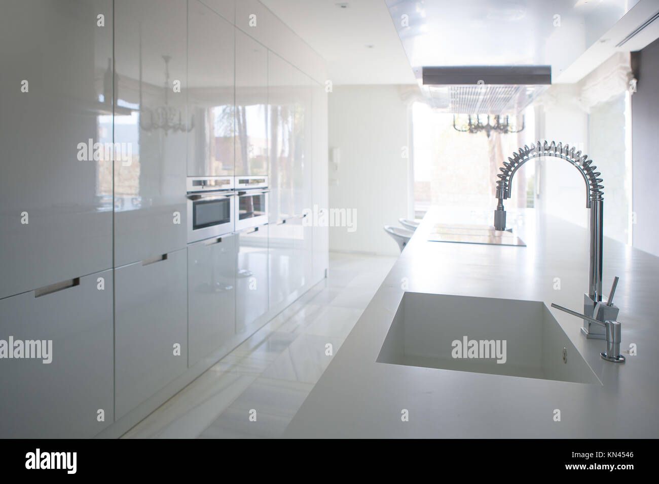 Modern white kitchen perspective with integrated bench sink ...