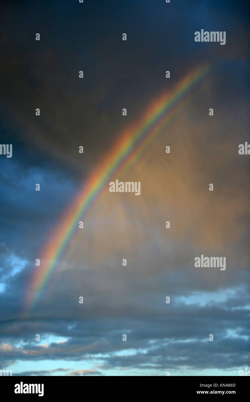 A colorful rainbow in a cloudy sky. - Stock Image