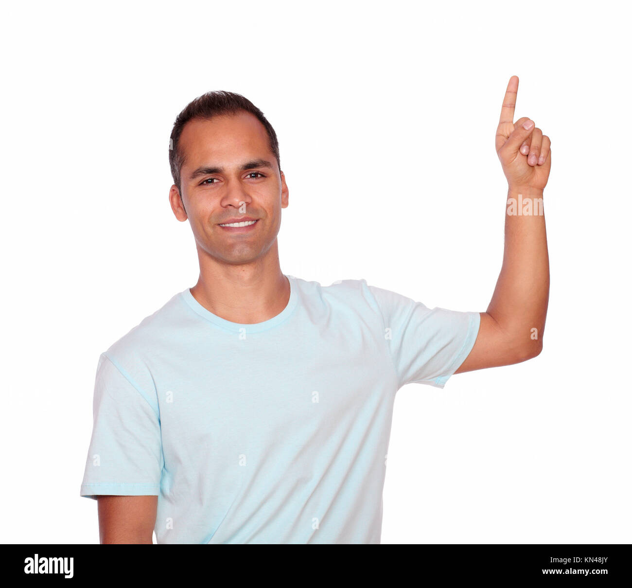 Portrait of an attractive young man on blue t-shirt pointing up on isolated background - copyspace. - Stock Image