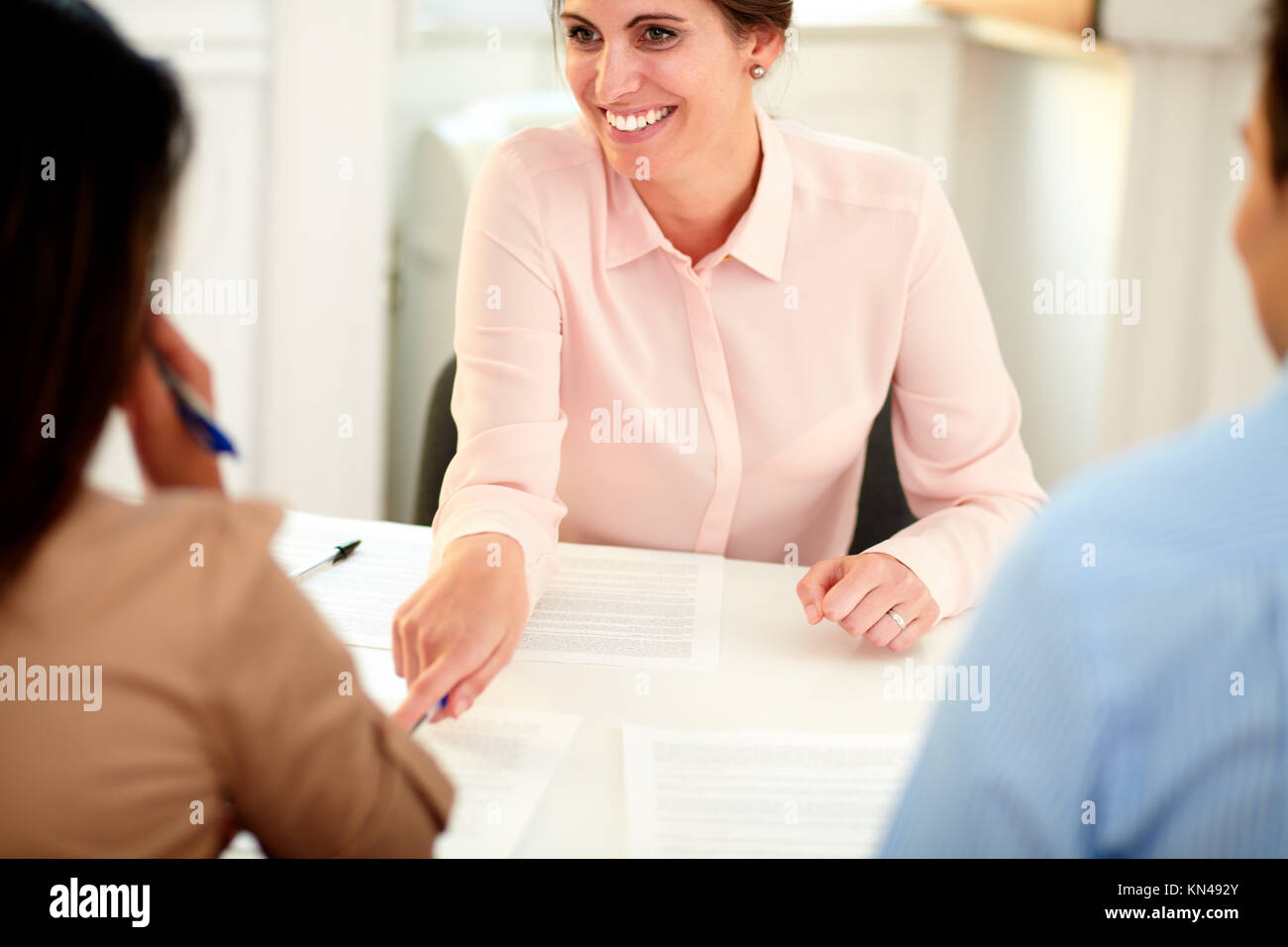 Portrait of young female bank manager working on agreement contract and explaining the application form to a young - Stock Image