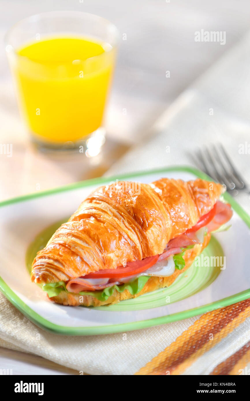 croissant with salad, ham and tomatoes. - Stock Image