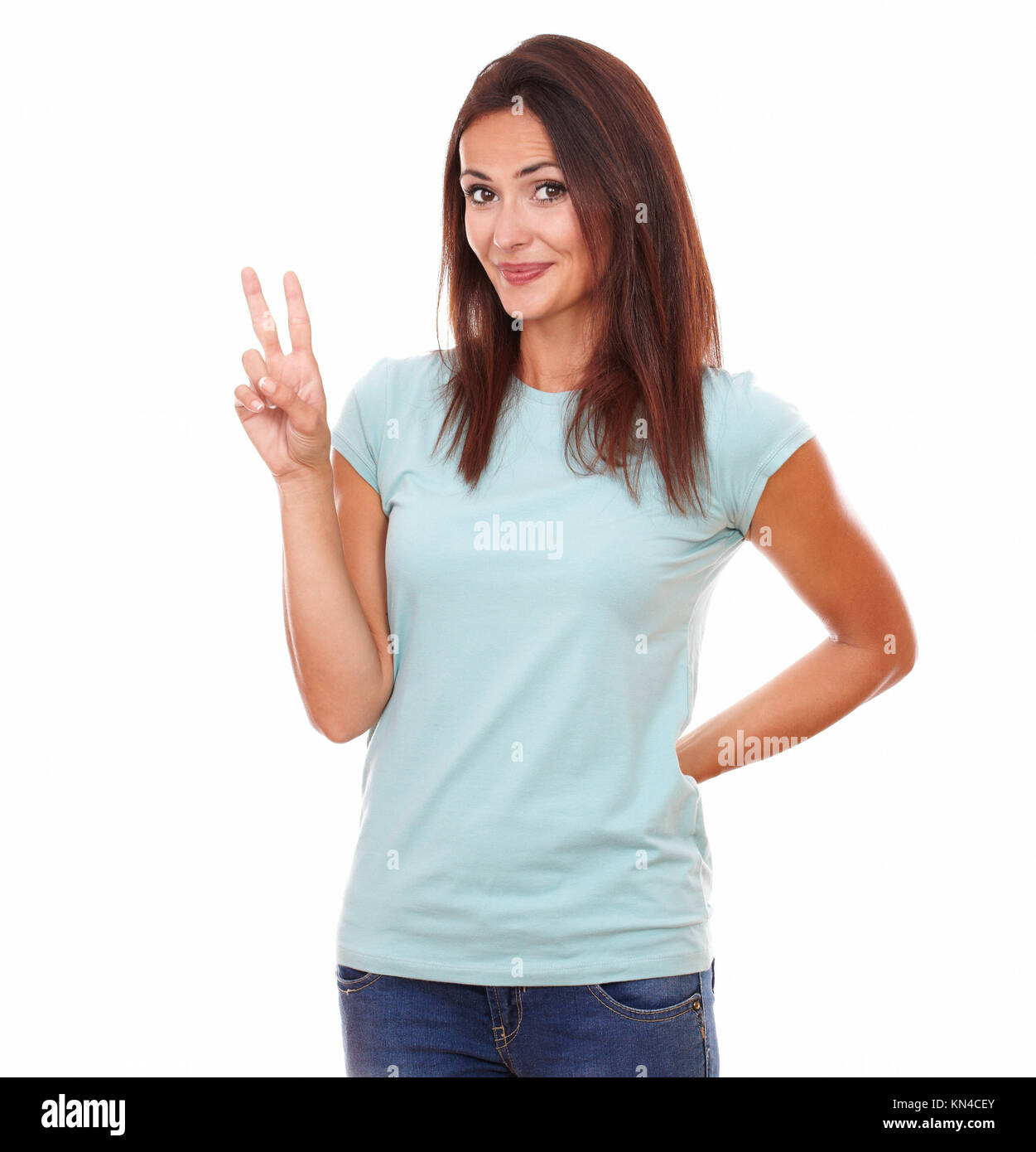 Portrait of 30-35 years friendly lovely woman on blue t-shirt with winning sign smiling at you while standing on - Stock Image