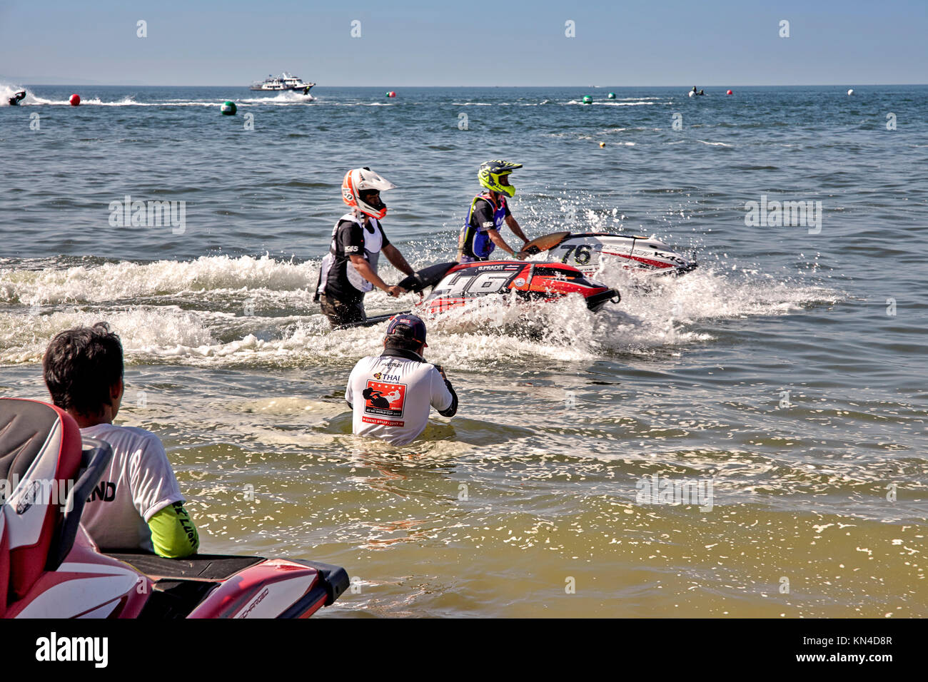 Intrepid and resourceful photographer on location and  waist deep in water taking photos at a Jet Ski water sport - Stock Image