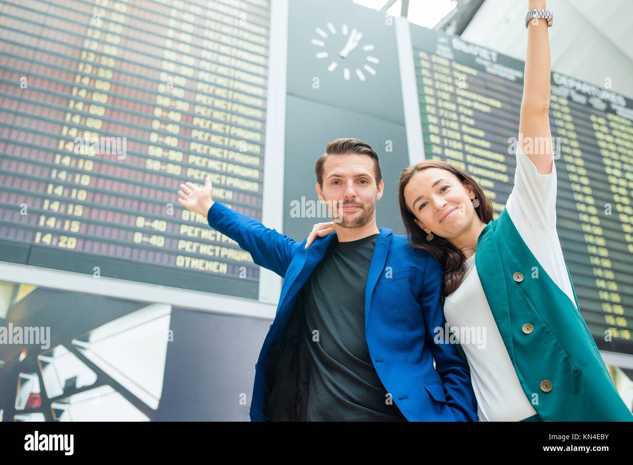 Portrait of young family in front of flight information board at airport Stock Photo