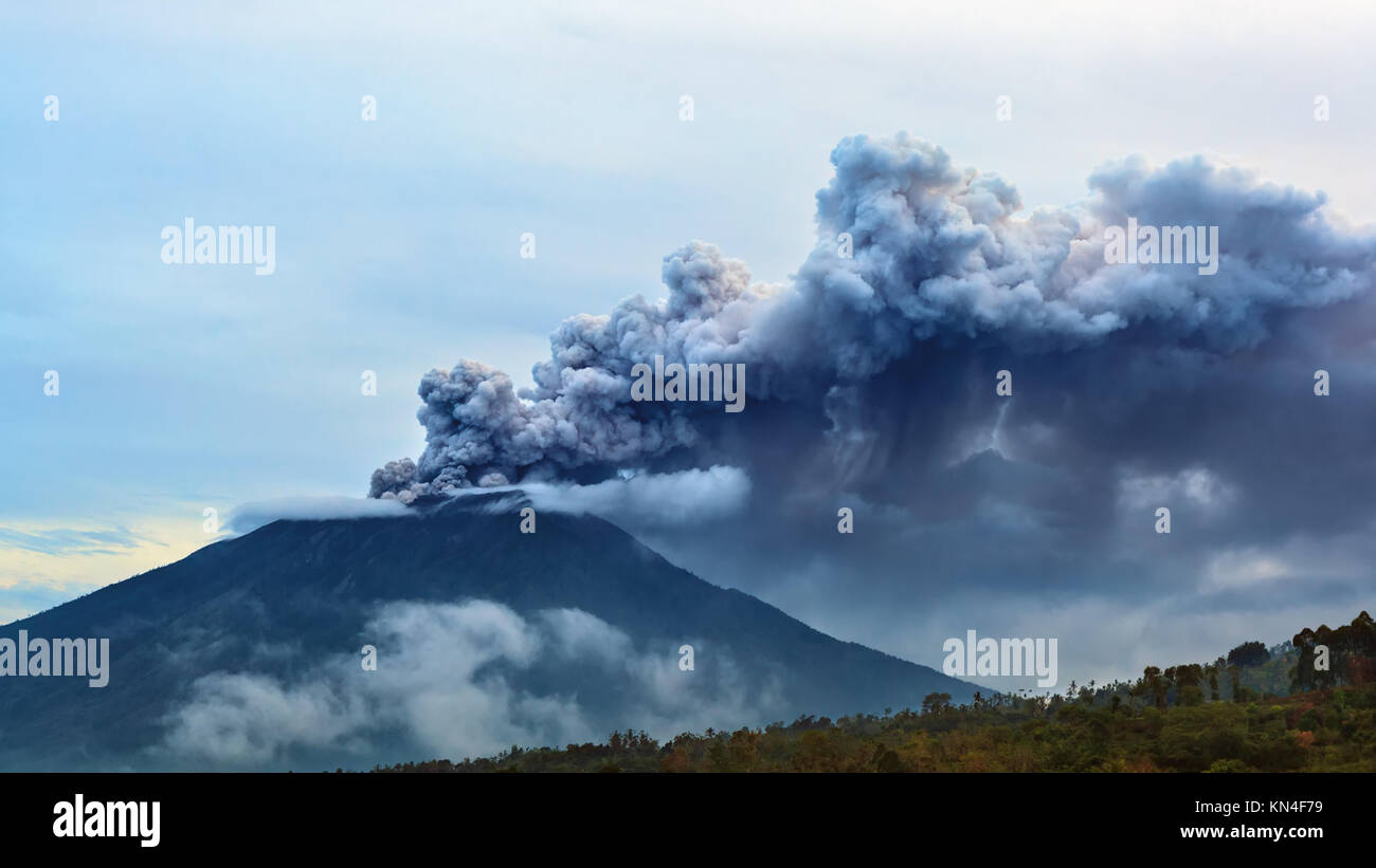 Mount Agung erupting plume. During volcano eruption thousands of people was evacuated from dangerous zone. Airline - Stock Image