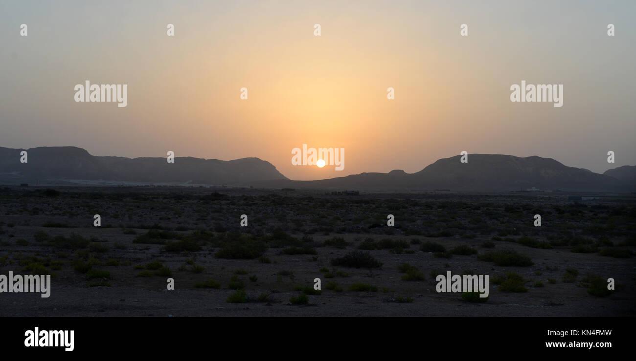 Sunset setting acorss the vast desert on Central Oman - Stock Image