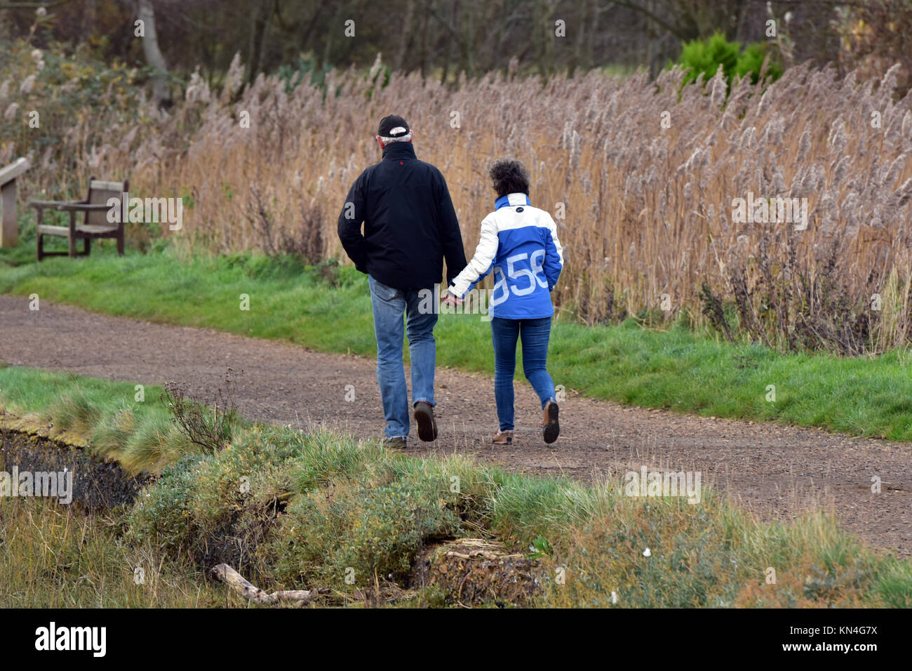 a trendy or classically dressed middle aged couple walking along a footpath next to some reeds and a river on a - Stock Image