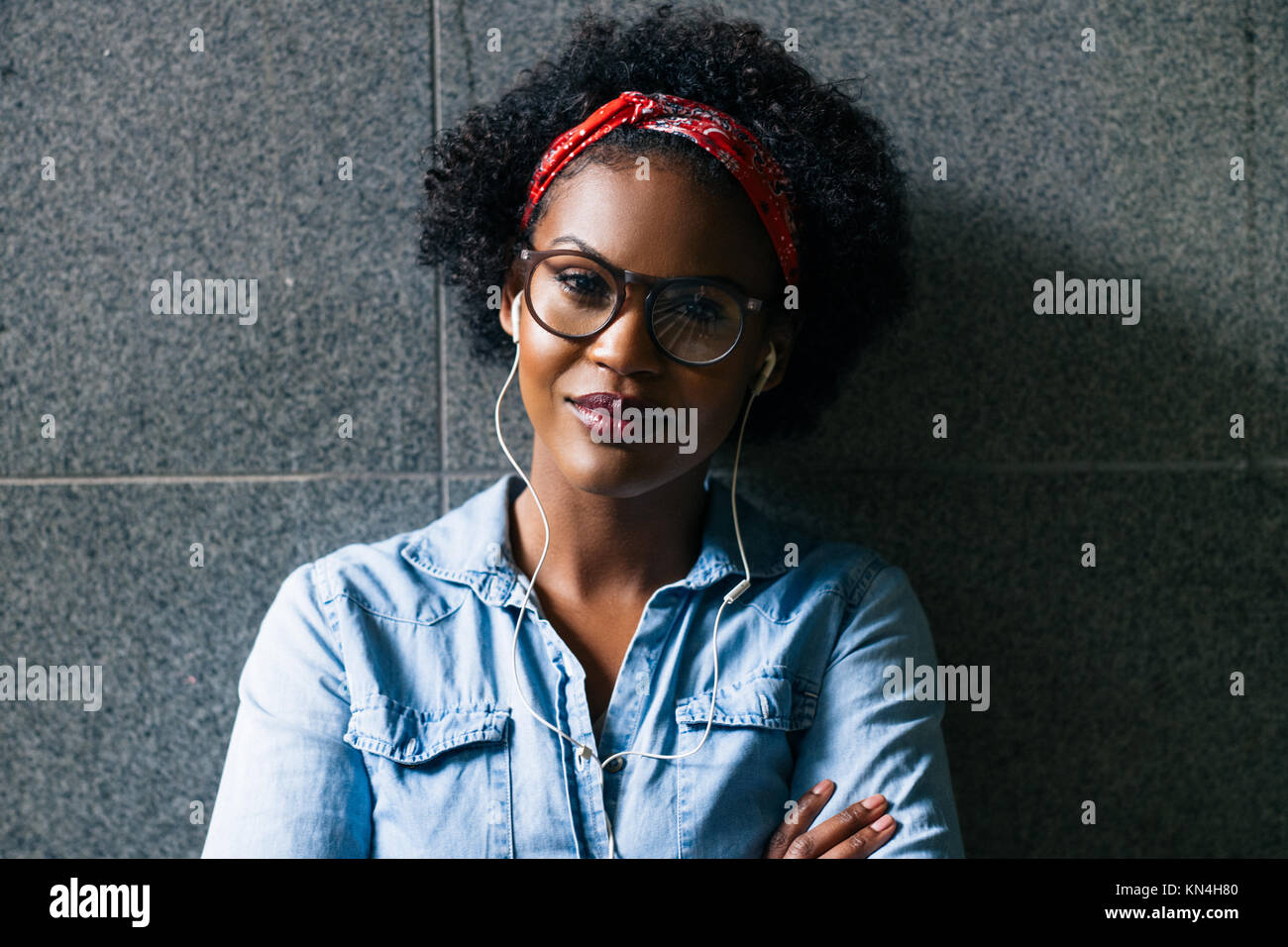 Stylishly dressed young African woman wearing glasses standing confidently with her arms crossed against a wall Stock Photo