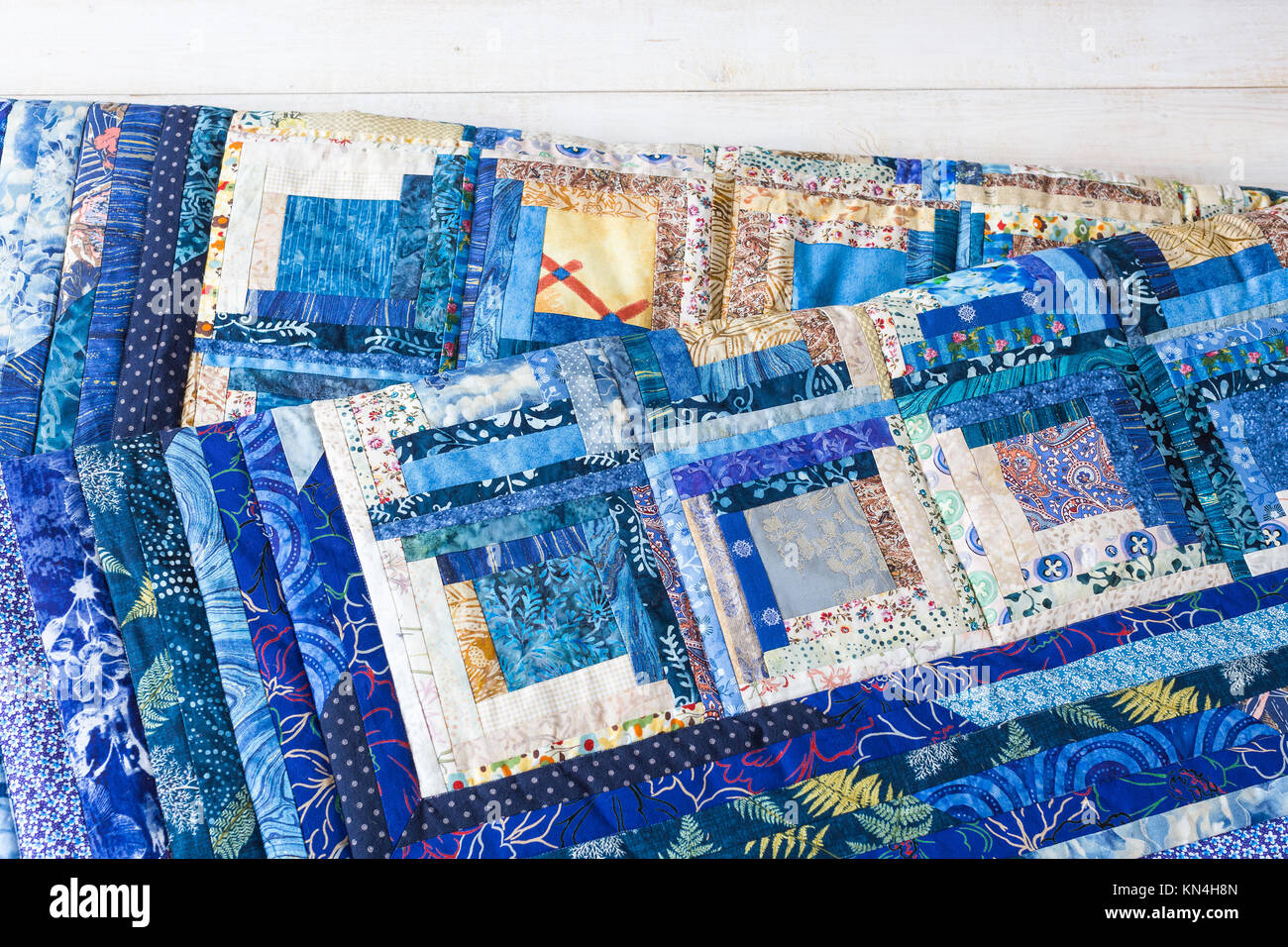 cosiness, comfort, design, homemade, quilting, hobby concept - warm cosy blankets made of colorful textile pieces - Stock Image