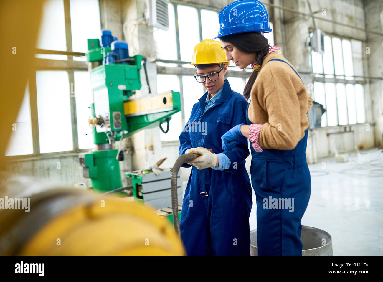 Machine Operators Solving Problem Together - Stock Image